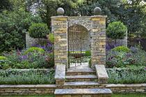 Metal gate between dry-stone piers, stone steps, half-domed stone niche, raised beds with Nepeta racemosa 'Walker's Low', Astrantia major 'Venice', Salvia nemorosa 'Caradonna', Rosa 'De Resht', Rosa '...