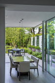 View from inside house to table and chairs on limestone patio outside, Pittosporum tobira in tall containers against wall