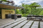 Outdoor kitchen and dining area, pleached mulberry espalier trees above wooden benches and table with tomatoes and herbs