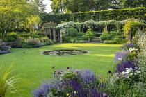 View across circular water lily pond in lawn to rose pergola, Rosa 'Francis E. Lester', Nepeta racemosa 'Walker's Low', Salvia nemorosa 'Caradonna', Paeonia lactiflora 'Jan van Leeuwen'