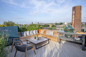 Outdoor kitchen on London roof terrace, chairs by Patrick Norguet, cushions on built-in wooden benches, barbecue grill