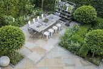 Table and chairs on York stone patio, Prunus lusitanica 'Angustifolia' standard lollipop trees, low clipped box hedges, pots on shelves, roses, astrantia, geranium, Alchemilla mollis, Erigeron karvins...