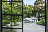 Table and chairs on York stone patio, Prunus lusitanica 'Angustifolia' standard lollipop trees, low clipped box hedges, pots on shelves, roses, Erigeron karvinskianus, view from inside, Sorbus cashmir...
