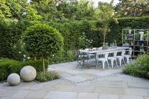 Table and chairs on York stone patio, Prunus lusitanica 'Angustifolia' standard lollipop trees, low clipped box hedges, pots on shelves, roses, Erigeron karvinskianus, Sorbus cashmiriana