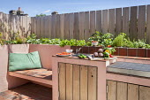 Outdoor kitchen and grill, built-in bench, cushion, wooden fence, herbs in raised bed, storage cupboards