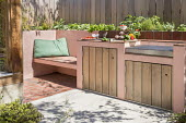 Outdoor kitchen and grill, built-in bench, cushion, wooden fence, herbs in raised bed, storage cupboards, concrete patio