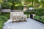 Wooden table and chairs on stone patio, clipped yew hedges, formal rill and waterfall, steps, glass screen