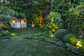 Circular astroturf lawns, view to summerhouse, clipped box domes, lit camellia