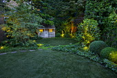 Circular astroturf lawns, view to summerhouse, clipped box domes, lit evergreen and amelanchier