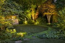 Uplit Acer palmatum, Acer palmatrum, stepping stone path around edge of circular astroturf lawn, view to summerhouse, Soleirolia soleirolii