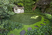 Stepping stone path around edge of circular astroturf lawn, view to summerhouse