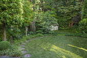 Stepping stone path around edge of circular astroturf lawns, view to summerhouse