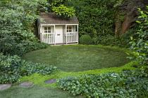 Stepping stone path around edge of circular astroturf lawn, view to summerhouse, Soleirolia soleirolii