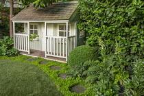 Wendy House in shady garden, stepping stone path around edge of circular astroturf lawns,