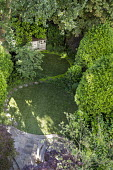 Circular astroturf lawns, stepping stone path, clipped bay trees