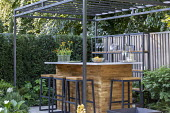 Black pergola over outdoor bar on terrace, yew hedge