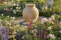 Large terracotta urn in circular terrace, Rosa 'Gentle Hermione', Perovskia 'Blue Spire', Ammi majus, Centranthus ruber 'Albus', Salvia nemorosa 'Caradonna', Achillea 'Lachsschonheit'