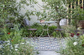 Table and chairs on mosaic tiled patio, apple trees