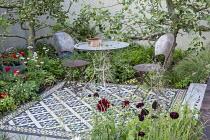 Table and chairs on mosaic tiled patio, apple trees, Scabiosa atropurpurea 'Black Knight'
