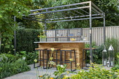Black pergola over outdoor bar on terrace, tall metal lanterns, agapanthus