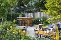 Black pergola over outdoor bar on terrace, Ilex crenata 'Blondie', Geum 'Totally Tangerine', eremurus, Achillea 'Credo', Carpinus betulus