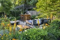 Black pergola over outdoor bar on terrace, Ilex crenata 'Blondie', Geum 'Totally Tangerine', eremurus, Achillea 'Credo', Acer cappadocicum, Carpinus betulus