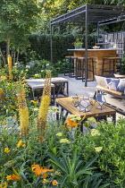 Black pergola over outdoor bar on terrace, Ilex crenata 'Blondie', Geum 'Totally Tangerine', eremurus, Achillea 'Credo', Acer cappadocicum