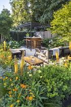 Black pergola over outdoor bar on terrace, tall metal lanterns, Ilex crenata 'Blondie', Geum 'Totally Tangerine', eremurus, Achillea 'Credo'