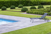 Recliner chair on stone paving by swimming pool, clipped box hedges, Cor-Ten Steel steps in lawn, mounds of Taxus baccata