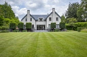 View across lawn with mowing stripes towards house, pleached hornbeam topiary