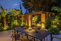 Succulents in glass terrariums on table lit at night, converted garage, timber screens around jacuzzi, Dicksonia antarctica, Pittosporum tobira