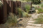 Ammophila arenaria in gravel border at side of house, wooden bench against retaining wooden wall