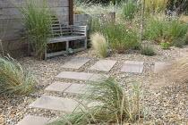 Wooden Lutyens bench, stepping stones in gravel, Ammophila arenaria, Stipa tenuissima