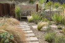 Stepping stone path across gravel, Verbena bonariensis, Anemanthele lessoniana, Stipa tenuissima, wooden Lutyens bench