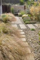 Stepping stone path across gravel leading to wooden Lutyens bench, Anemanthele lessoniana, Calamagrostis × acutiflora 'Karl Foerster', Verbena bonariensis, Stipa tenuissima, Lavandula angustifolia 'H...