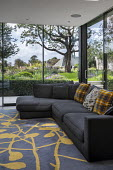 Sofa with cushions in conservatory, rug, view to contemporary garden outside