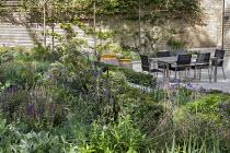 Table and chairs on patio, Agastache 'Blackadder', Salvia nemorosa 'Caradonna', Selinum wallichianum