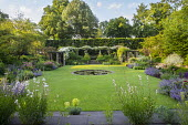 View across circular water lily pond in lawn to rose pergola, Rosa 'Francis E. Lester', Gaura lindheimeri, Nepeta racemosa 'Walker's Low'
