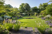 View across circular water lily pond in lawn to rose pergola with Rosa 'Francis E. Lester', Gaura lindheimeri, Nepeta racemosa 'Walker's Low'