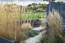 Calamagrostis × acutiflora 'Karl Foerster' screen, painted wooden screen, Nepeta racemosa 'Walker's Low', Stipa tenuissima, formal pool, lavender in Cor-Ten steel raised bed