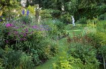 Grass path leading to nymph statue, Geranium psilostemon