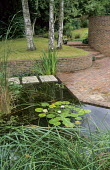 Raised lawn, brick wall and paving, stepping stone path across pond, water lilies