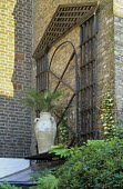 Trellis arch on wall, terracotta container with palm on shelf above roof