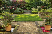 Lawn, gravel, brick edging, pools, containers with astilbes, steps, box edged borders