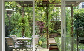 View from inside through patio doors to table and chairs under pergola outside, patio heater, Acer palmatum