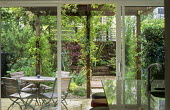 View from inside through patio doors to table and chairs under pergola outside, Acer palmatum