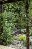 Timber-edged raised bed, gravel garden, sisyrinchium, railway sleepers, Hakonechloa macra 'Aureola'