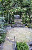 Overview of town garden, circular paved area, steps to terrace, rose pergola, fountain by Sally Price, box balls in containers, Rosa 'Noisette Carnée'