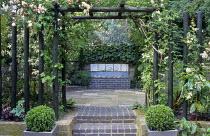 Paved terrace, rose pergola, Rosa 'Noisette Carnée', Cornus alba 'Elegantissima', Viburnum cinnamomifolium, fountain by Sally Price, box balls in pots
