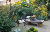 Parasol over gravel, butcher's block table, containers with thymes, chairs, bowl with box balls, Catalpa x erubescens